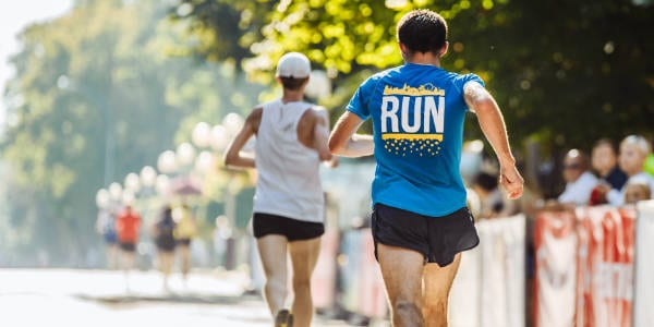 The backs of two male runners, running in a marathon